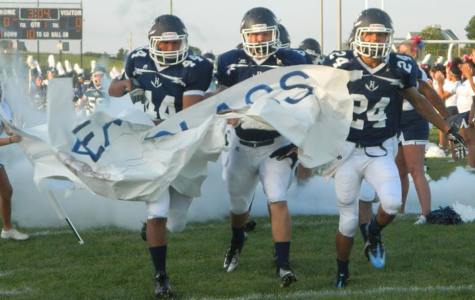 Seniors Campbell Rutherford, Isaiah Hertzler, and junior Luis Pinedo-Lafferty break through the banner at the E.C. Glass home game on August 29.