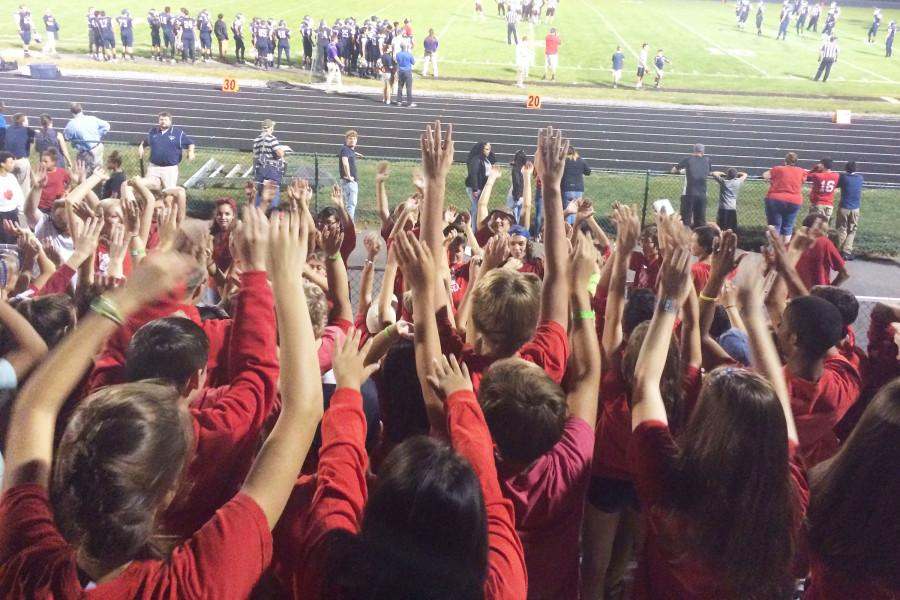 The+Red+Sea+gets+their+hands+up+in+support+of+the+team.+
