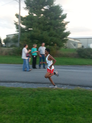 Mehari Gidey approaches the finish line at the Fairgrounds 5k course while pacing his fellow runners that are close behind.