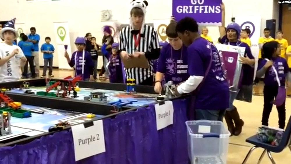 Two students work on their robot after the race.