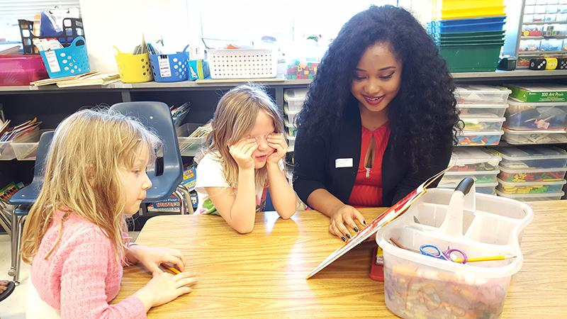 Junior Alanna Whitefield reads with Waterman Elementary School students.