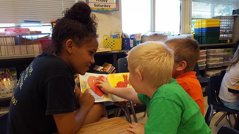 Sophmore Monalisa Gebretsadik reads to Waterman Elementary School students.