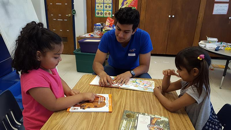 Exchange student Joaquin Orozco reads with Waterman Elementary School students.