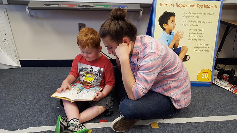 Senior Austin Swift reads to a Waterman Elementary School student.
