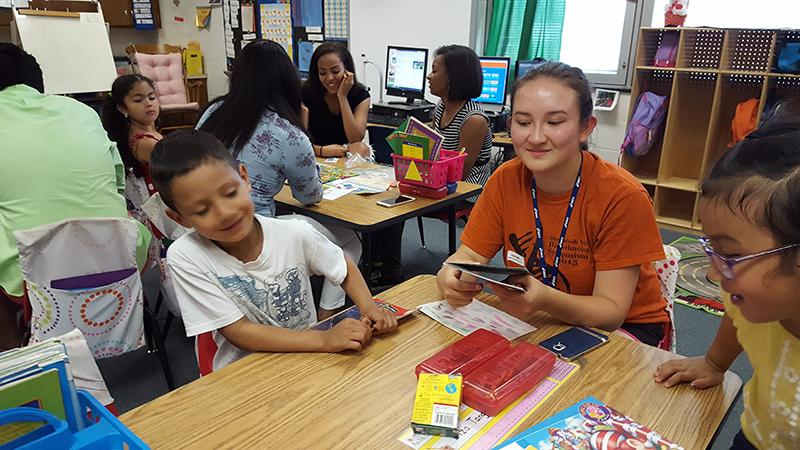 Junior Athena Benton reads to Spotswood Elementary School Kindergarden students.