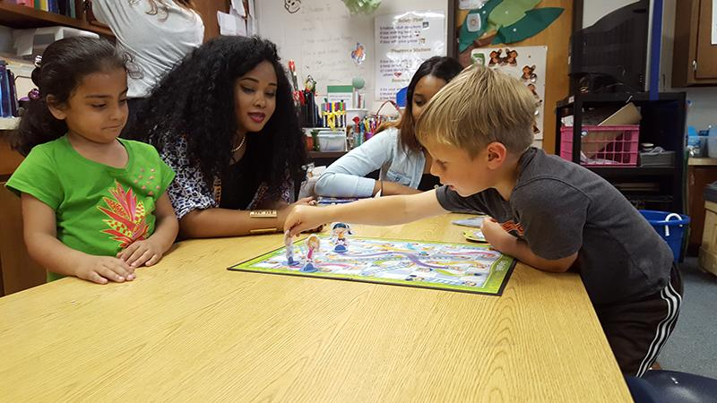 Senior Jasmine Rodriguez and junior Alanna Whitfield play a game with Spotswood Elementary school students.