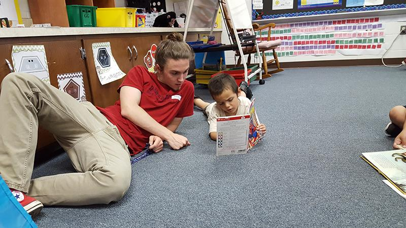 Senior Austin Swift reads with a Spotswood Elementary school student.