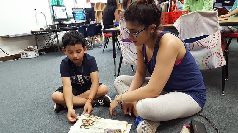 Senior Sako Haji reads with a Spotswood Elementary school student.