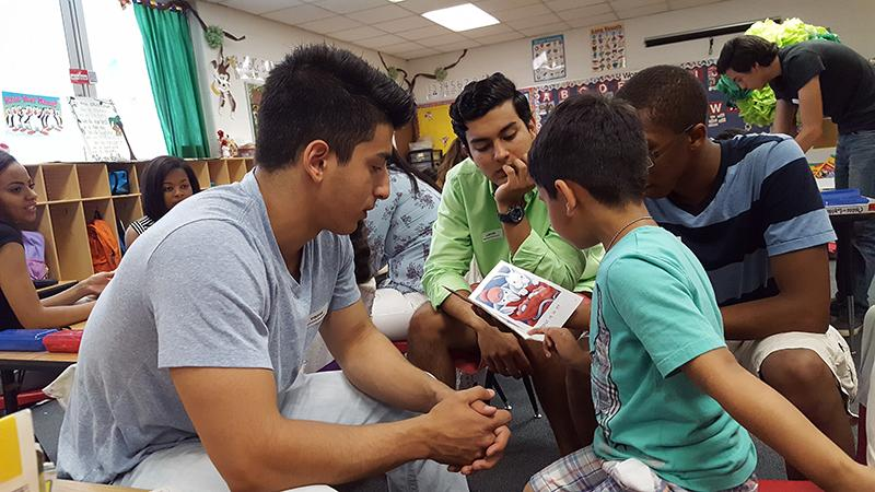 Senior Mund Abdula, exchange student Joaquin Orozco, and junior Kyel Towler read to a kindergarden student at Spotswood Elementary.