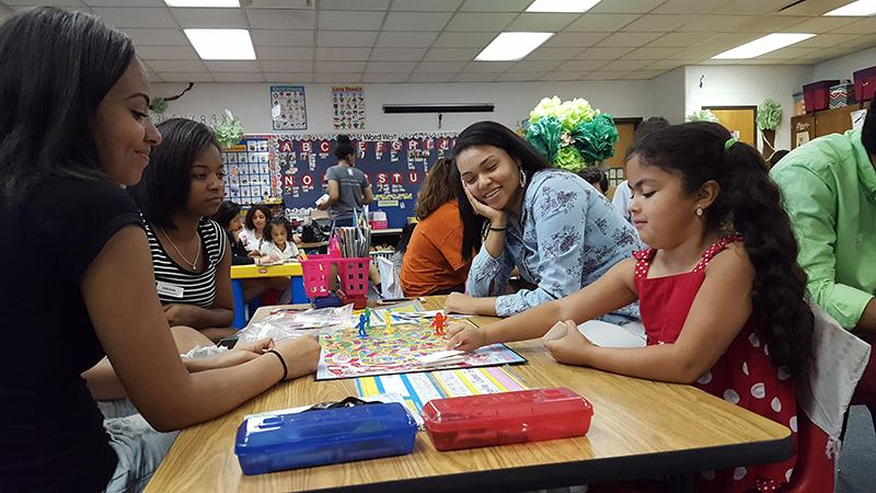 Seniors Taylor Maclon, Carrissa Washington, and junior Monee Willingham play a game with a kindergarden student from Spotswood Elementary.