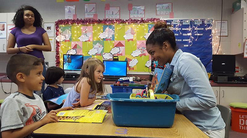 Senior Jasmine Rodriguez reads to Stone Spring Elementary School students.