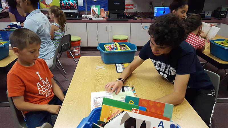 Senior Diego Avila reads with a Stone Spring Elementary School student.