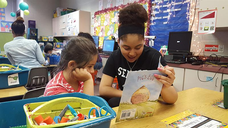 Senior Joslyan Vega reads to a Stone Spring Elementary School student.