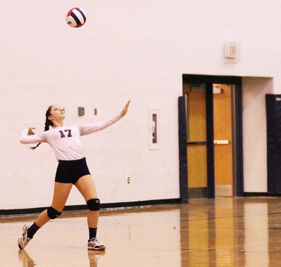 Abby McCollum serves the ball the Judges.
