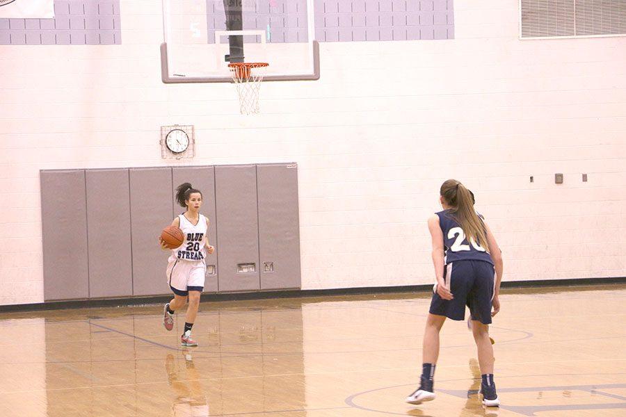 Jane Thompson dribbles down the court.