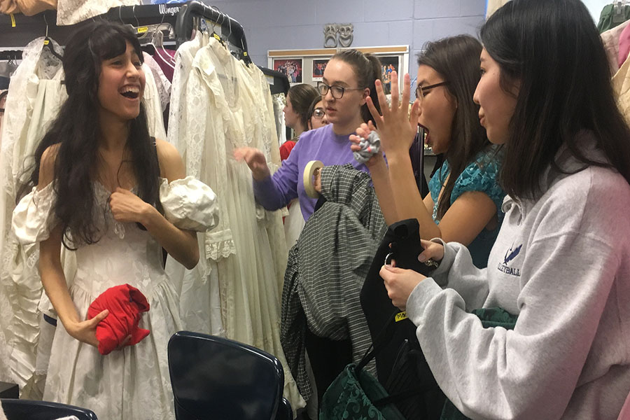 A group of students from the cast prepares their costumes before going out to practice