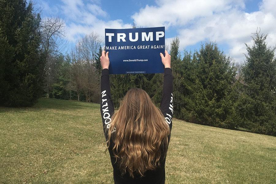 A girl holds up a pro-Trump sign