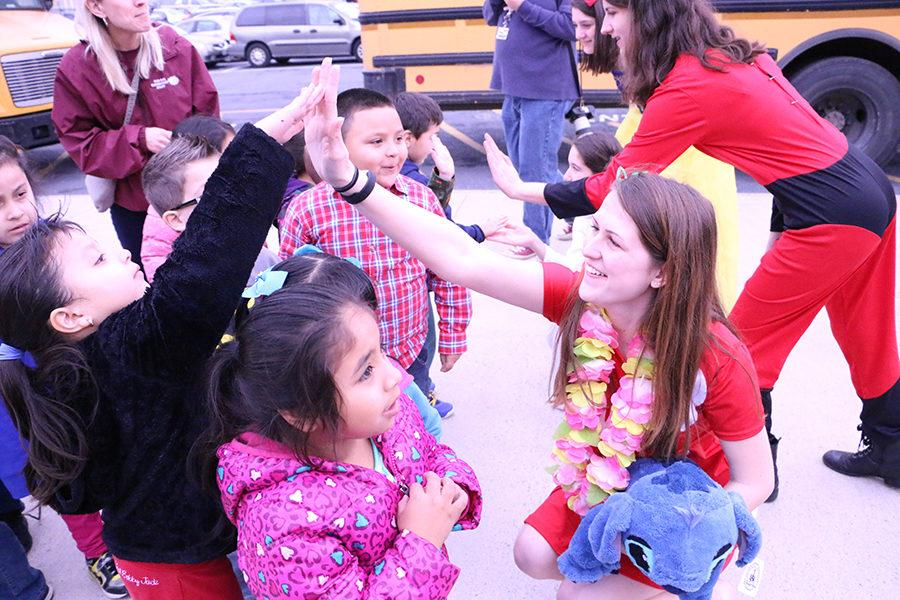 Junior Natalie Pittington, dressed as Lilo from Lilo and Stitch talks to kids as they arrive for the Tiny Tots concert.