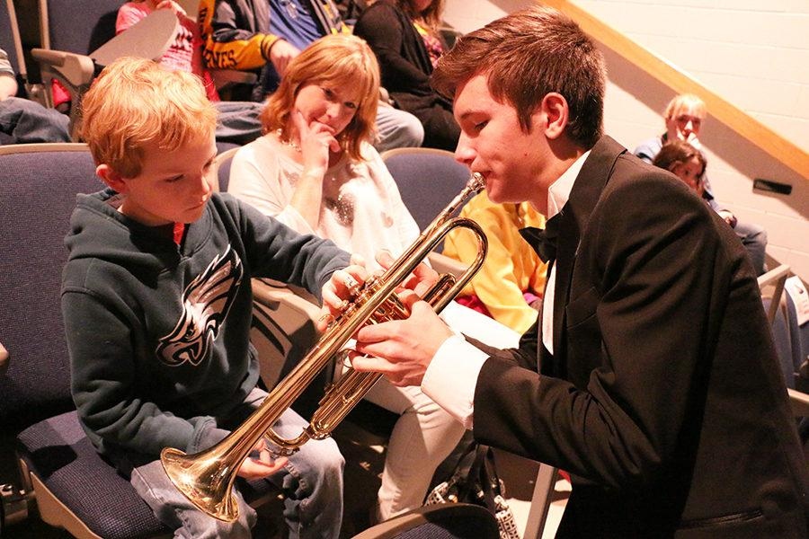 Sophomore Michael Komlev gives a local elementary student a chance to hear the different sounds each key on his trumpet makes when pushed.