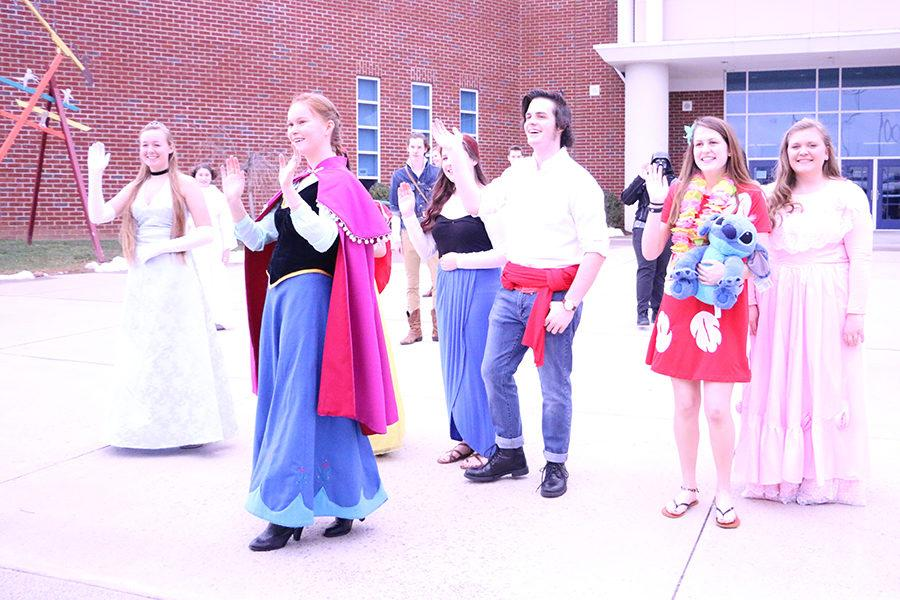 Band+members+wait+outside+the+school+to+greet+elementary+school+students+dressed+as+various+Disney+characters.