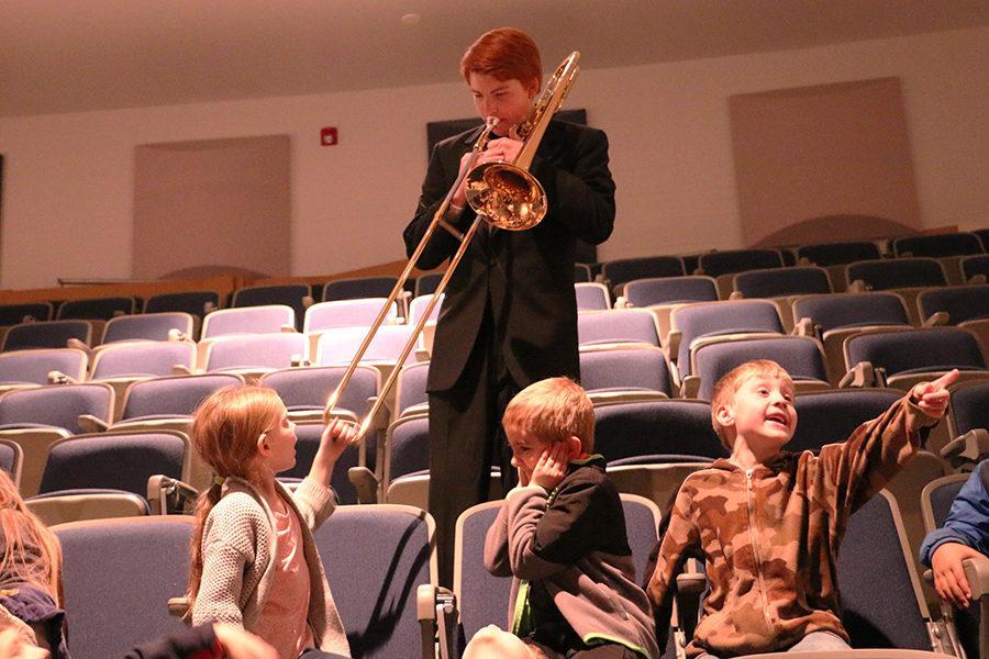 Senior Jonathan Aigner lets a student test how far his trombone will slide.