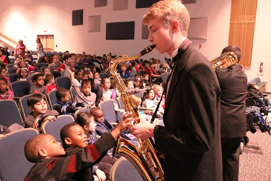 Senior Philip Hart, one member of the Jazz Ensemble, lets two students play his saxophone for him during Tiny Tots two years ago.