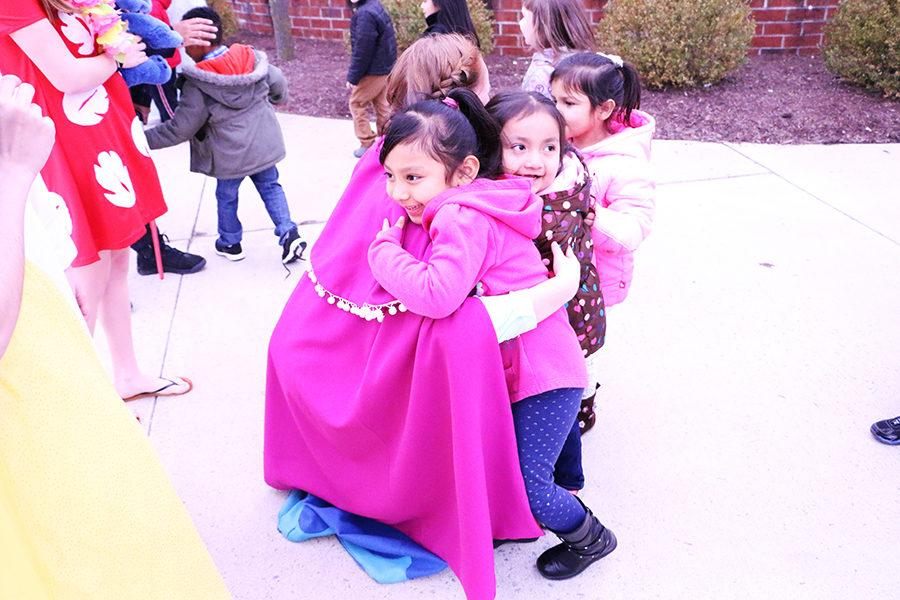 Junior Emily Werner hugs two girls as Ana from Frozen.