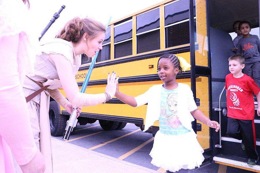 Senior Cecily Lawton greets Stone Spring Elementary students as they get off their bus.
