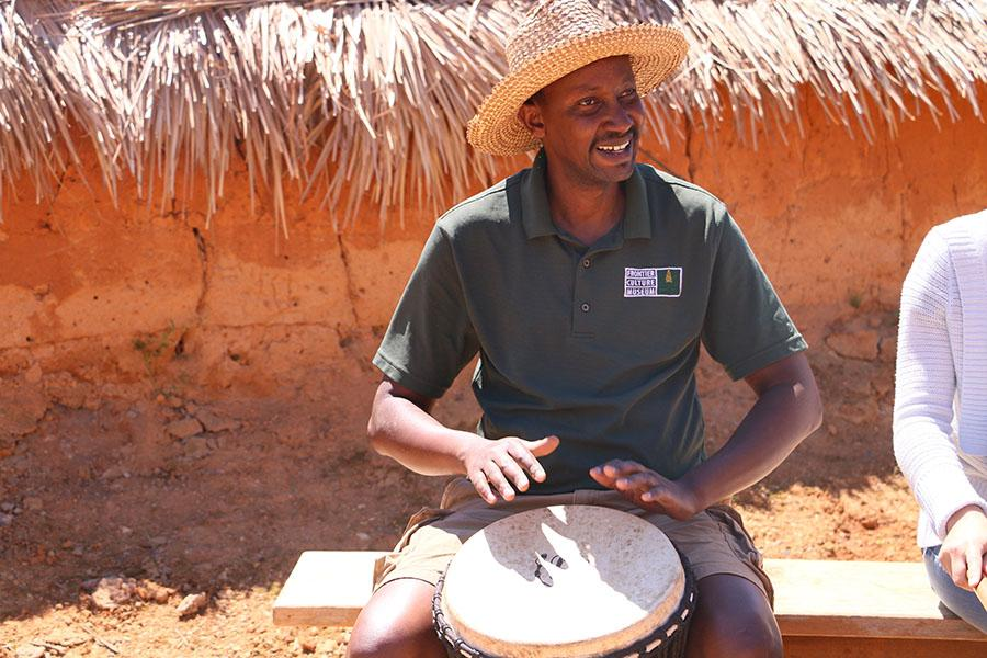 The instructor shows the group how to play a beat on the drums.