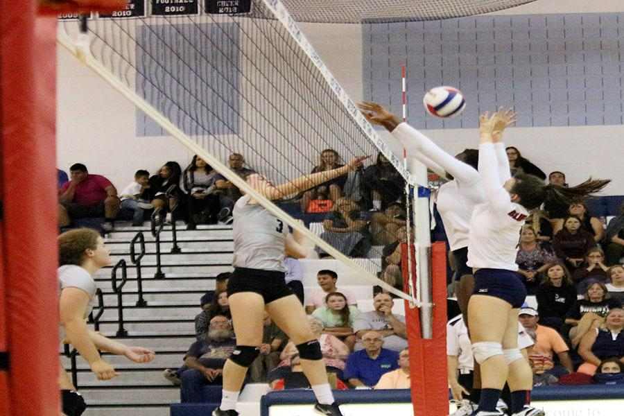 Senior Olivia Comer and sophomore Atilia Thomas jump for a block during the fourth and final set of the game.