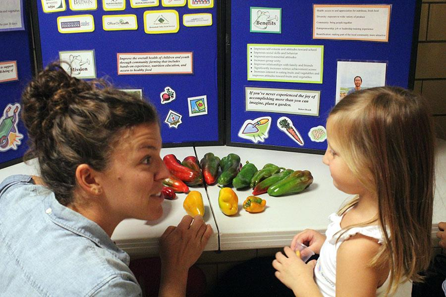 Laura Smith displays the varying colors of peppers to another Keister student.