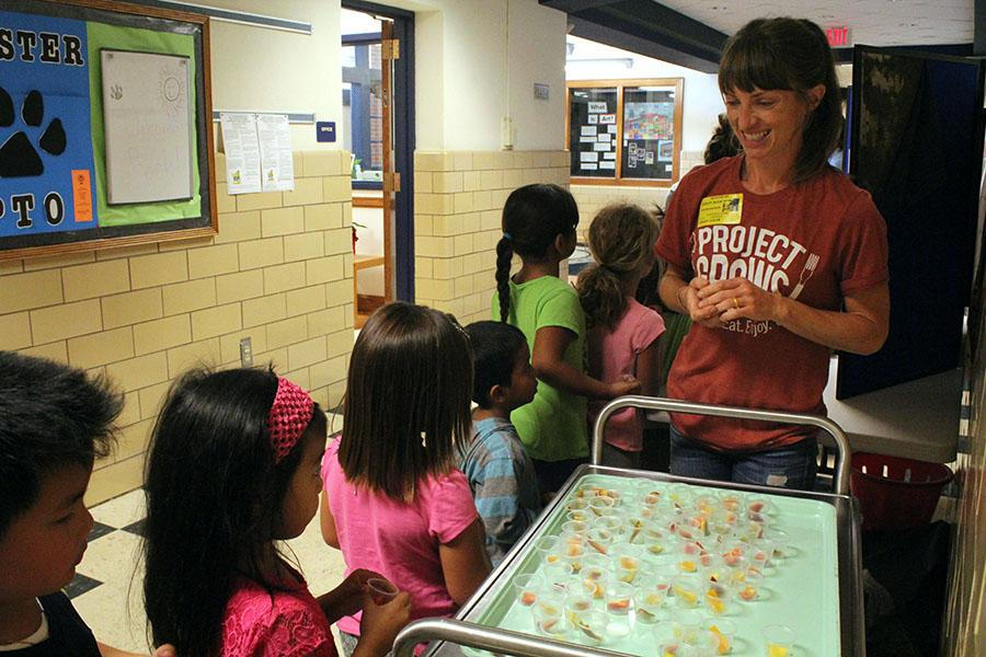 Alicia Cooley mans the tasting cart as students file in and out of the lunchroom.