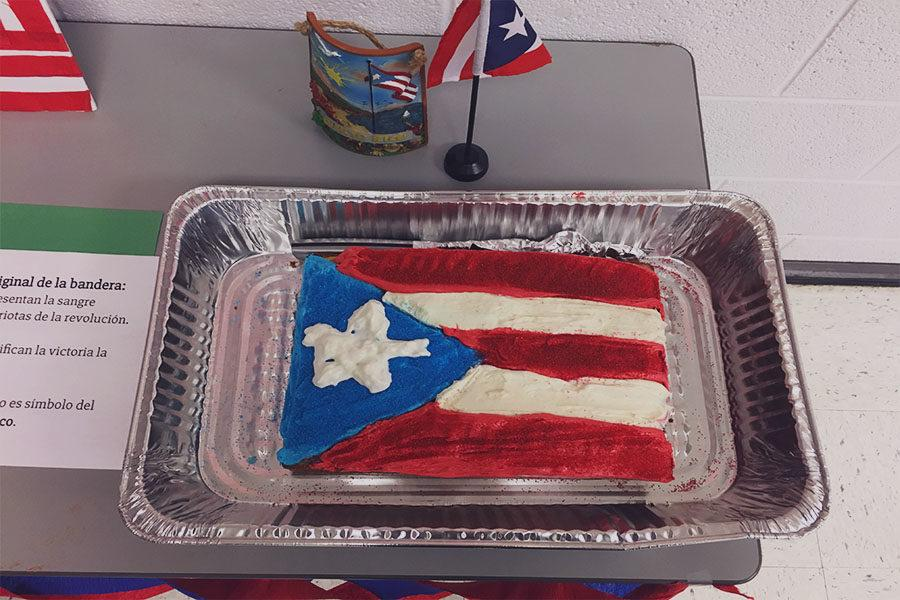 Foreign language students display a cake with a Puerto Rican flag.