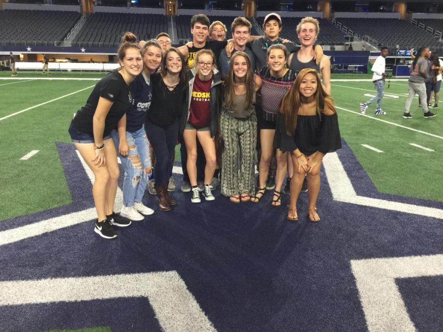 The group of 13 Newsstreak staff members stands together on the field at the Dallas Cowboys stadium, one of the highlights of the trip.