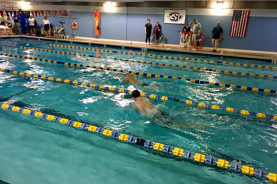 Junior James Henderson competes in the 100 meter breaststroke.