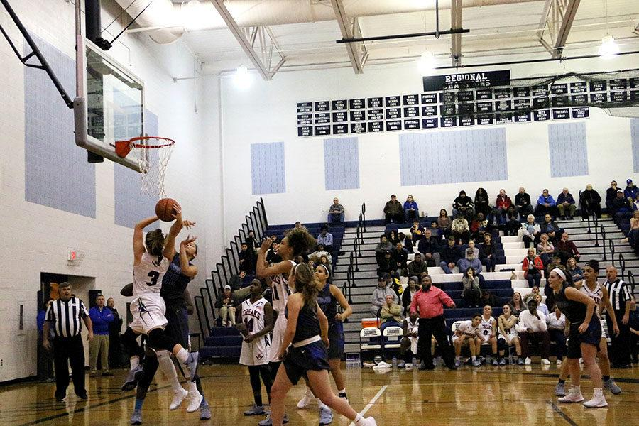 Senior Constance Komara takes the shot, going up against a Spotswood player.