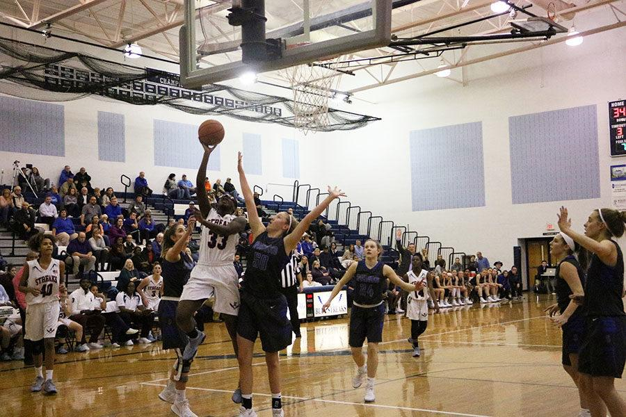 Sophomore Atilia Thomas attempts a layup overtop of a defender from Spotswood.
