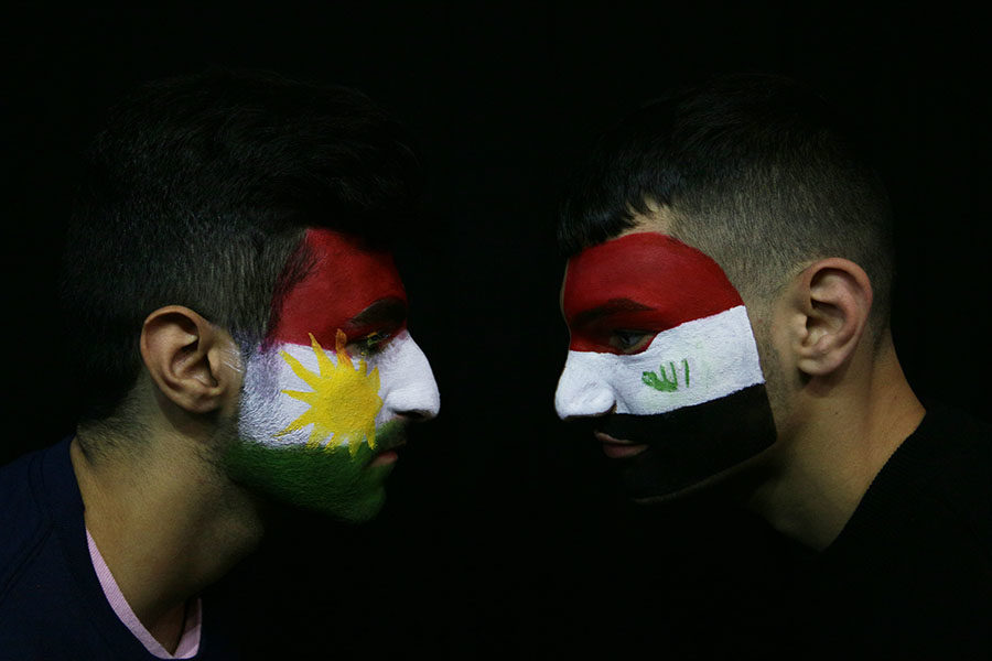 Senior Lawan Rasul (left) and junior Sadeeq Saffo (right) face each other with the Kurdish and Iraqi flags painted respectively on their faces.