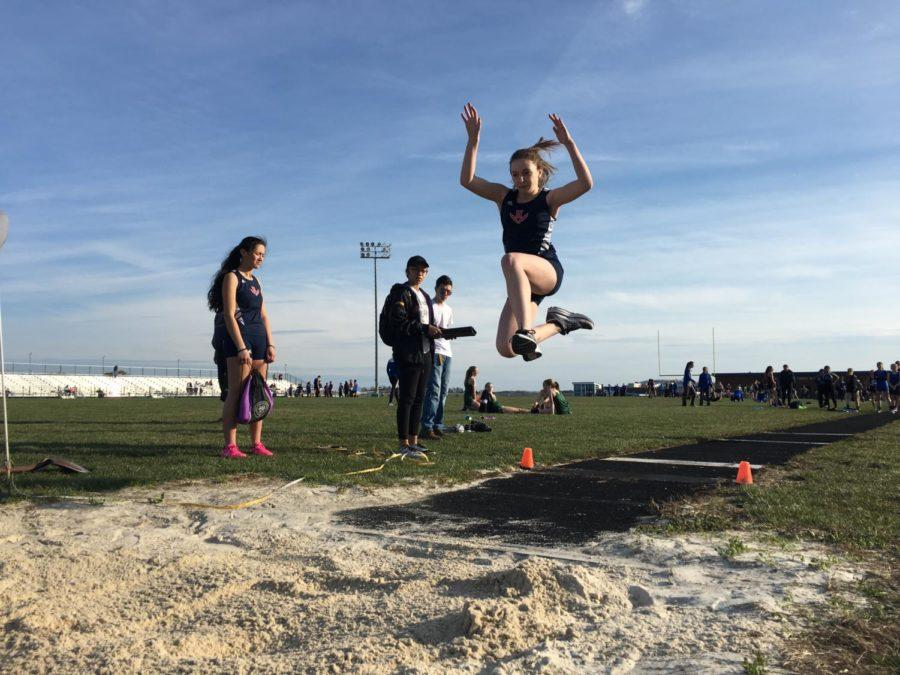 Freshman Sydney Shaver jumps into the pit during the long jump competition.