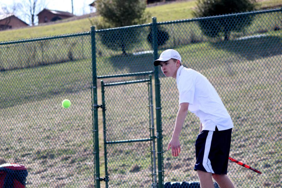 Junior John Collier returns the ball in his doubles team with Junior Tobias Yoder.