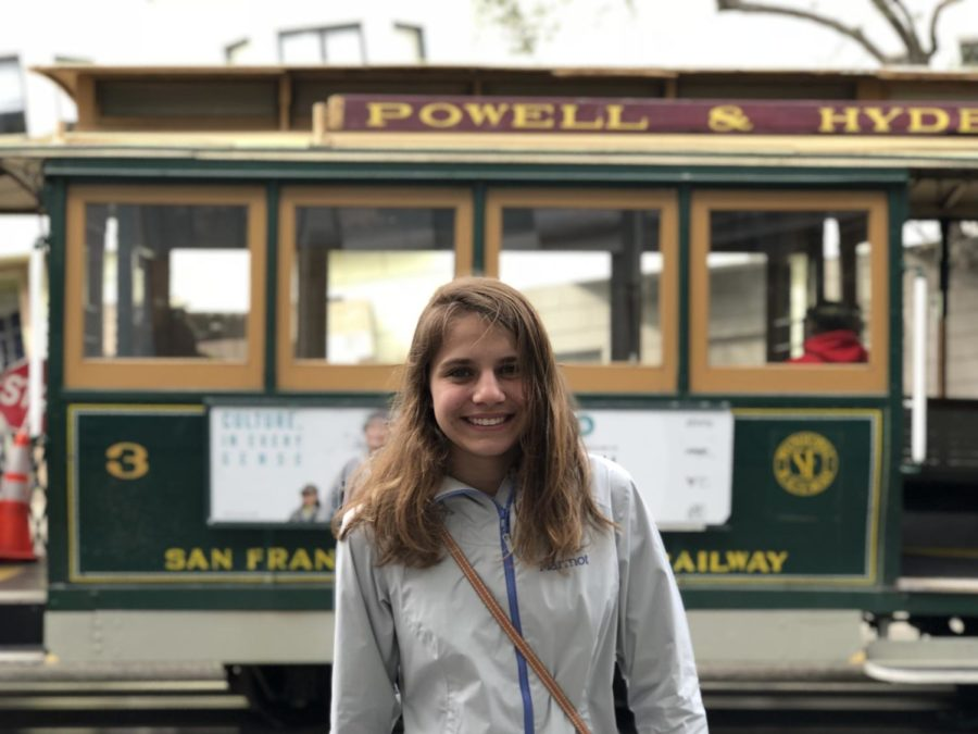 The writer stands in front of a trolley car while on a trip to San Francisco