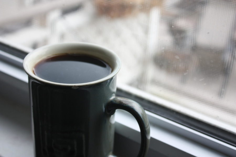 A cup of coffee sits in a windowsill