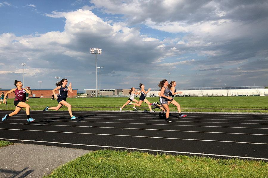 Seniors Carissa Roberts and Sydney Harper and freshman Elena Luhn run the 100 meter dash. Roberts reflects on what made her last season great.