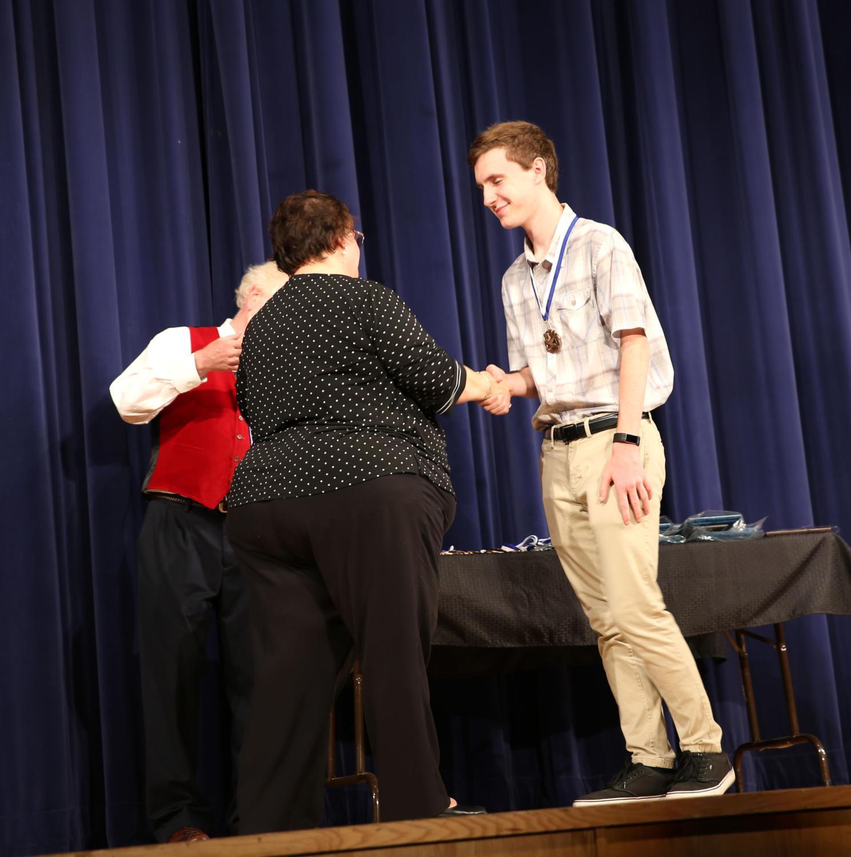 Senior+Josh+Lucas+shakes+hands+with+principal+Cynthia+Prieto+after+receiving+his+medal.+