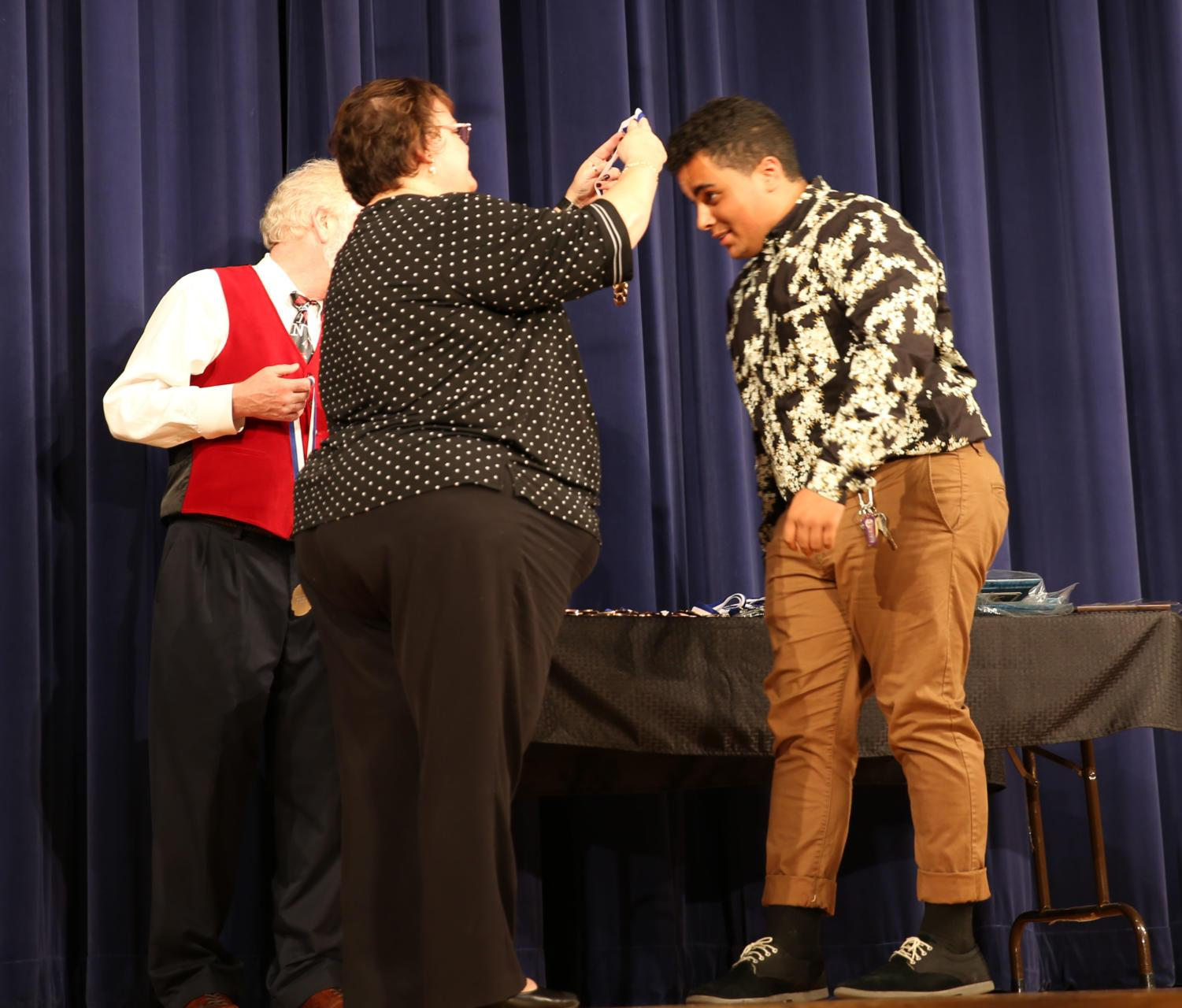 Principal+Cynthia+Prieto+puts+the+medal+around+the+neck+of+senior+Leomar+Lopez+after+he+is+recognized.+
