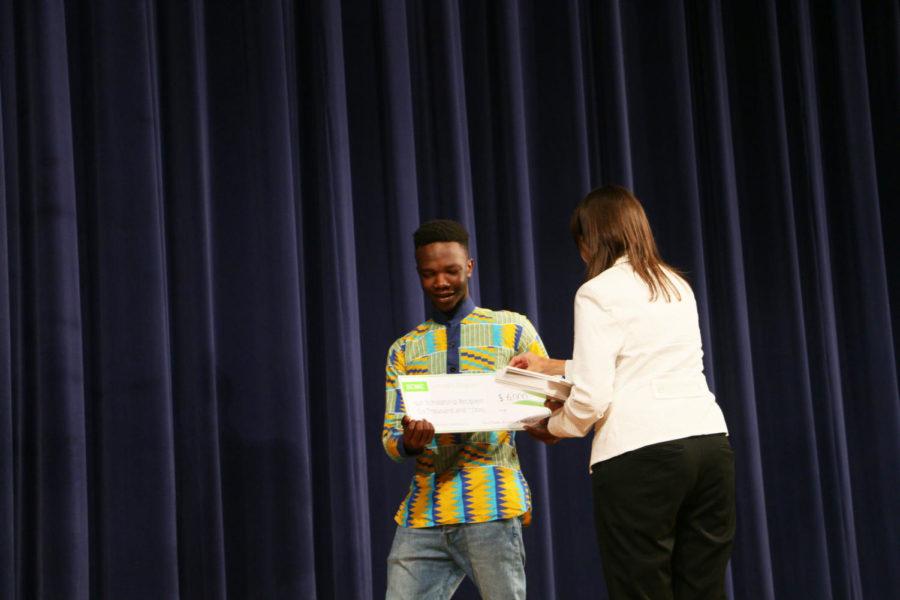 Guidance counselor Rachel Linden hands senior Evans Adam a check for an academic scholarship, as he attends Radford University this fall.