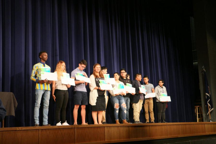 Seniors line up displaying their checks in their hands, as the 11 of them receive a scholarship for being an early college scholar.