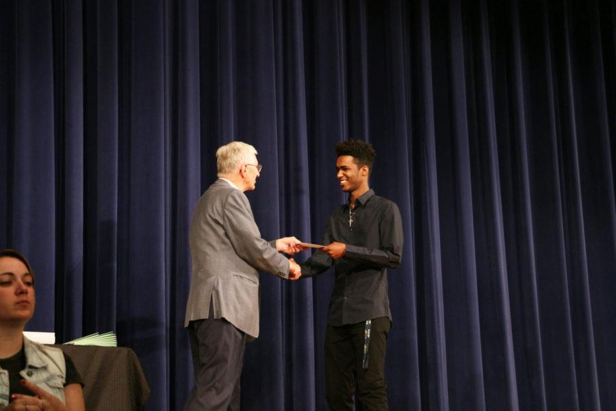Senior Mehari Gidey is handed the Kiwanis Raymond Dingledine Scholarship at the assembly.