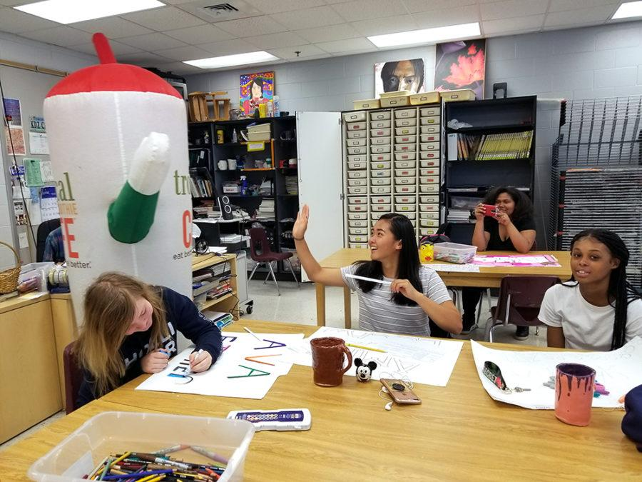 Freshman Amira Lucas high fives the smoothie mascot while smoothies are given out to her art class.