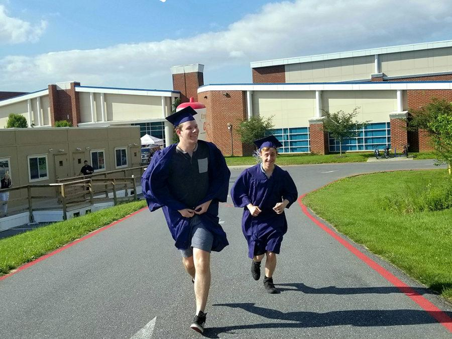 Seniors Corin Vogel and Joshua Lucas run up the hill past the smoothies to make it to their class picture. Seniors got to grab smoothies before the picture and bring them with them.